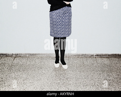 Young Woman With Chequered Skirt Standing In Front Of Wall Of Blue Tiles Berlin Germany - Stock Photo