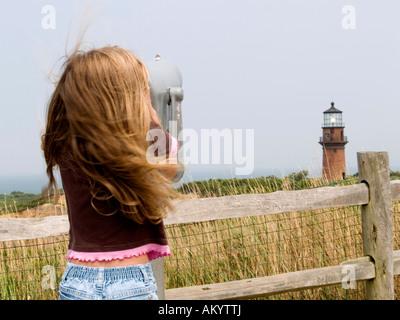 A little girl looks through coin operated binoculars to the Gay Head Lighthouse at Aquinnah, Martha's Vineyard Massachusetts - Stock Photo