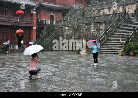 Tourists taking pictures in a temple, Wudangshan, China - Stock Photo