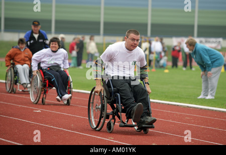 Handicapped man racing with a wheelchair - Stock Photo