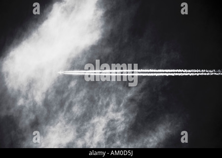 Commercial Airplane Leaving Vapor Trail In The Sky - Stock Photo