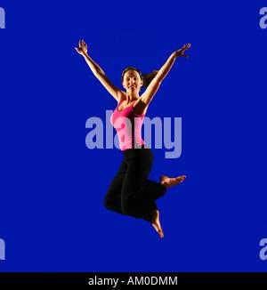 teenage girl jumping on blue background - Stock Photo