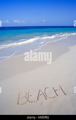 The word BEACH written on the sand on white tropical beach in Playa del Carmen, Cancun, Mexico - Stock Photo