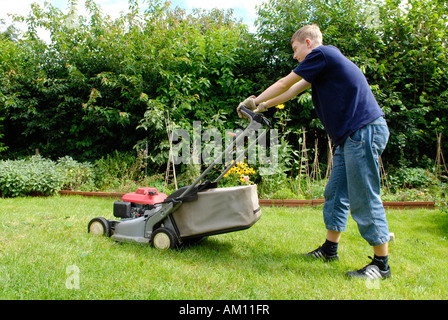 Teenager mowing lawn - Stock Photo