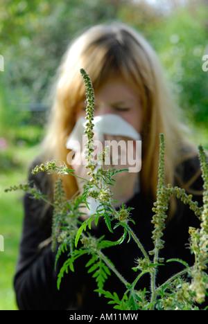 Woman reacting allergic to Ragweed - Stock Photo