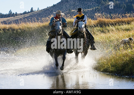 Cowboys riding in water, wildwest, Oregon, USA - Stock Photo