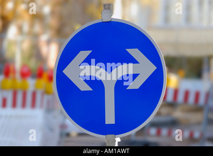 Traffic sign with two directional arrows in order to detour a road construction site - Stock Photo