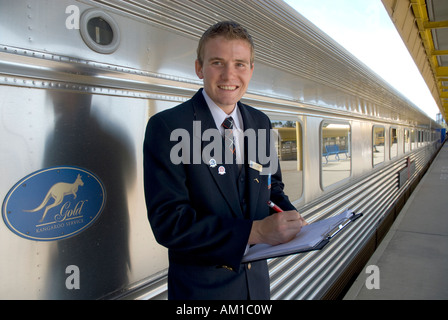 Conductor of the Ghan train waiting for passengers in the station of Adelaide, South Australia, Australia - Stock Photo