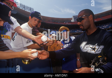 Professional Baseball player signing autographs and balls for young fans Dodger Stadium Los Angeles CA - Stock Photo