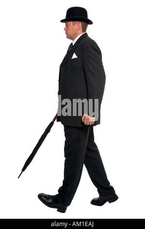 City businessman in pin striped suit wearing a bowler hat and carrying an umbrella as he walks along - Stock Photo
