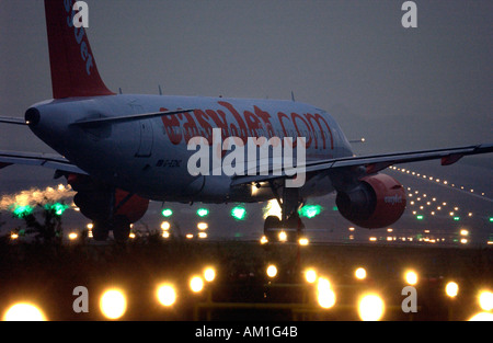 An EasyJet plane prepares for takeoff from London Gatwick airport runway at night - Stock Photo