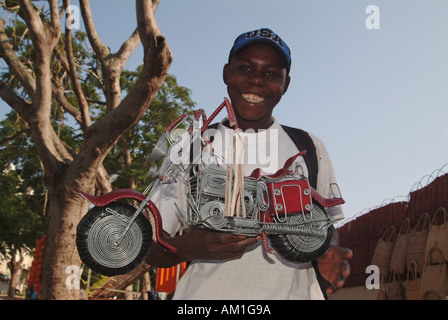 A young boy selling a handmade wire motorcycle in Maputo, Mozambique, Africa - Stock Photo