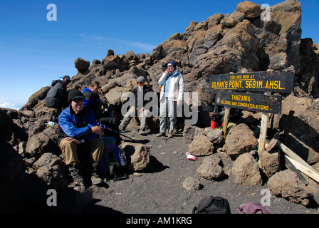 Successful group of mountaineers at the sign on the summit Gilman's Point (5681 m) crater rim Kilimanjaro Tanzania - Stock Photo