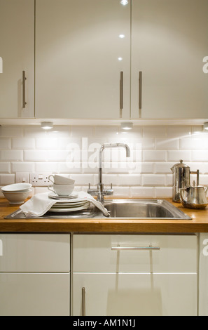 detail of kitchen sink and cupboards with running bond white tiles - Stock Photo