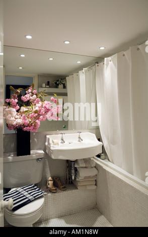Cherry blossom in tiled bathroom - Stock Photo