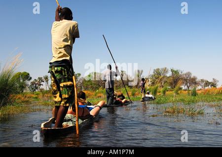 Locals in Mokoro dugoutboat on a tourist excursion in the Okavango Delta, Botswana - Stock Photo