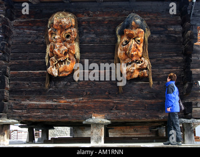 Women looks at a pair of oversized traditional wooden masks made of Swiss pine wood, Wiler, Loetschental, Valais, - Stock Photo