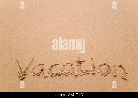 The word Vacation written in sand at the beach - Stock Photo