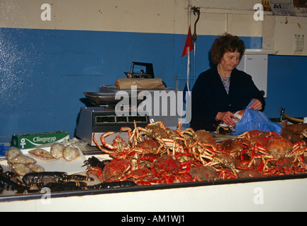 Lady fishmonger selling crabs and lobsters in the Fish Market, St Peter Port, Guernsey, Channel Islands - Stock Photo
