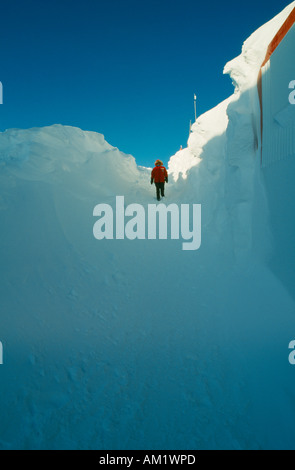 ANTARCTICA South Pole US Amundsen Scott South Pole Station Figure walking through high banks of drifted snow on - Stock Photo