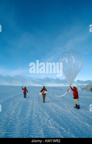 ANTARCTICA South Pole US Amundsen Scott South Pole Station Three figures launching a weather balloon to measure - Stock Photo