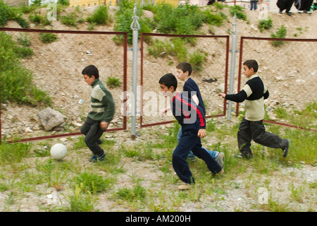 ARMENIA Vanadzor Four school age boys play soccer outdoors in weedy fenced play area run after ball in group - Stock Photo