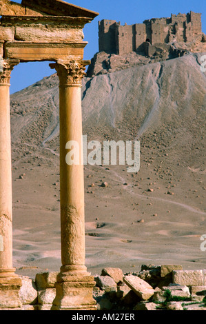 The ancient roman ruins of Palmyra Syria and Qalaat Ibn Maan Muslim castle in the background - Stock Photo