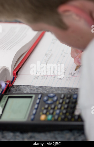 Student using calculator to do Algebra math homework - Stock Photo