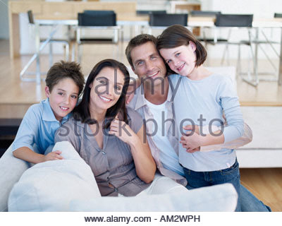 Man and woman with boy and girl sitting on sofa - Stock Photo