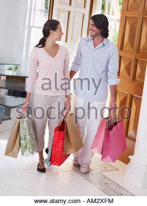 Couple entering home with shopping bags - Stock Photo