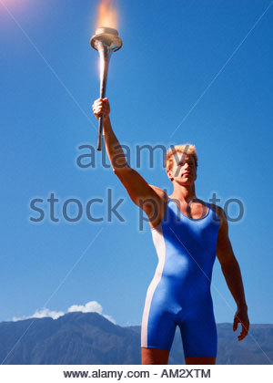 Athlete holding torch in scenic location - Stock Photo