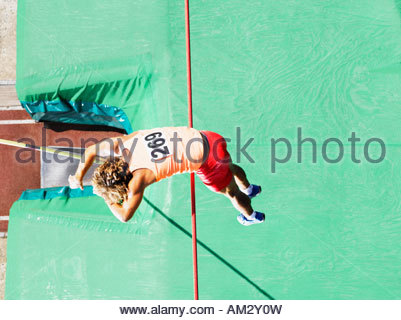 Athlete doing pole vault over a large mat - Stock Photo