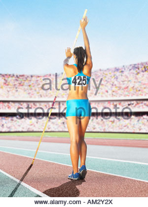 Athlete pole vaulting in an arena - Stock Photo