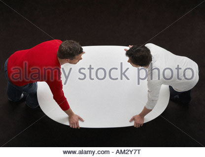Two men leaning over a table - Stock Photo