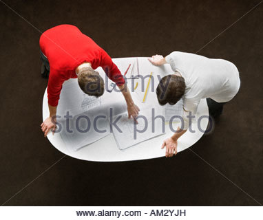 Two businessmen leaning over a table - Stock Photo