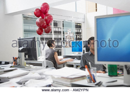Businesswoman at desk with balloons tied to chair and coworker in foreground - Stock Photo