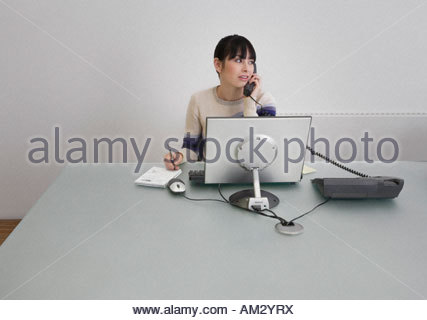Businesswoman on telephone in an office - Stock Photo