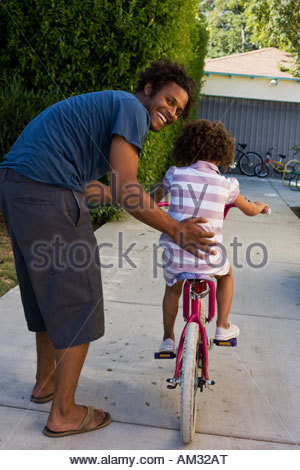Father teaching daughter to ride bicycle in driveway - Stock Photo