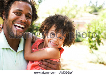 Man holding young girl outdoors smiling - Stock Photo