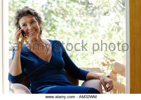 Woman on her mobile phone smiling indoors - Stock Photo