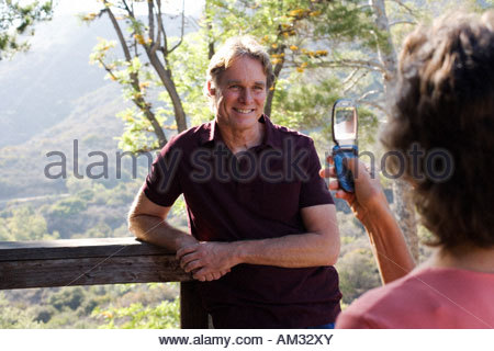 Woman taking picture with camera phone of man on staircase outdoors - Stock Photo