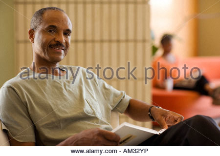 Man with book in living room with woman in background reading - Stock Photo
