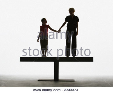 Woman and young girl holding hands on a plank - Stock Photo