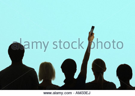 five people standing together with one holding up her mobile phone - Stock Photo