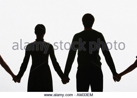 four people standing hand in hand with two out of shot - Stock Photo