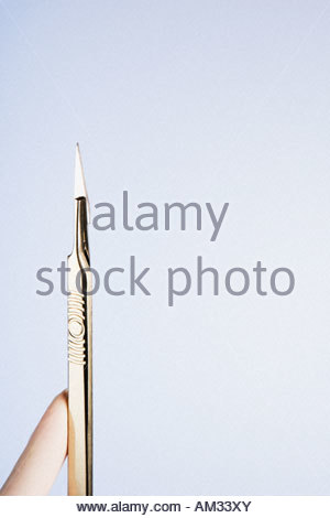 A gloved hand holding a scalpel - Stock Photo