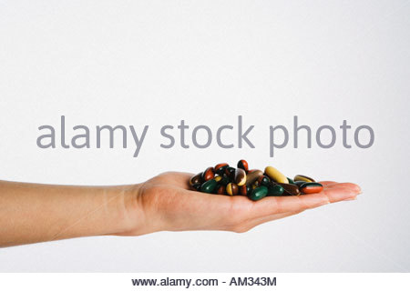 Hand holding pile of pills - Stock Photo