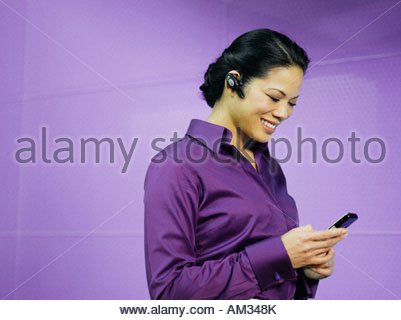 Businesswoman with mobile phone and earpiece in purple office - Stock Photo