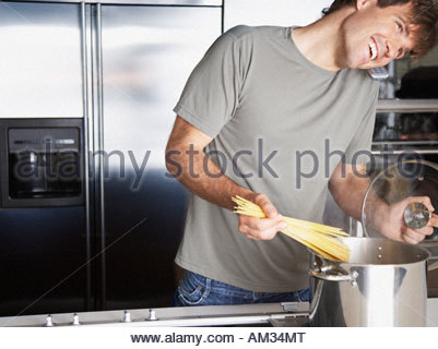 Man putting pasta into a cooking pot while on telephone - Stock Photo