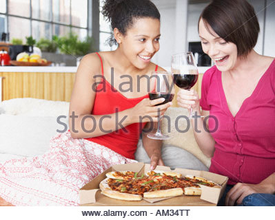 Two women with wine and pizza in a living room - Stock Photo